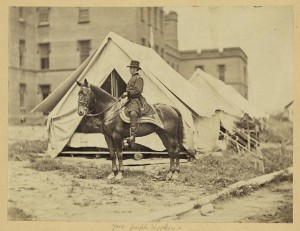 [Major-General Joseph Hooker, full-length portrait, seated on horse, facing left, wearing military uniform, two tents and large building in the background (between 1861 and 1865; LOC: LC-DIG-ppmsca-19394)