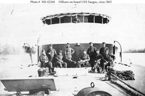 USS Saugus (1864-1891)  Officers pose on deck, in front of the gun turret, probably while the ship was serving on the James River, Virginia, in early 1865.  U.S. Naval Historical Center Photograph.