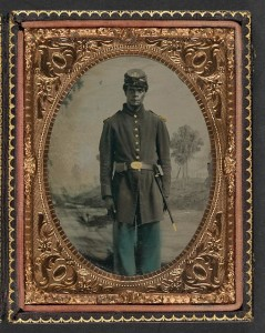 Unidentified African American soldier in Union uniform and Company B, 103rd Regiment forage cap with bayonet and scabbard in front of painted backdrop showing landscape with river] (between 1863 and 1865; LOC: LC-DIG-ppmsca-36988)