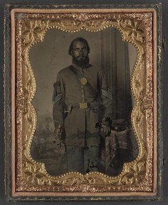 Unidentified African American soldier in Union infantry sergeant's uniform and black mourning ribbon with bayonet in front of painted backdrop (between 1863 and 1865; LOC:  LC-DIG-ppmsca-34365)