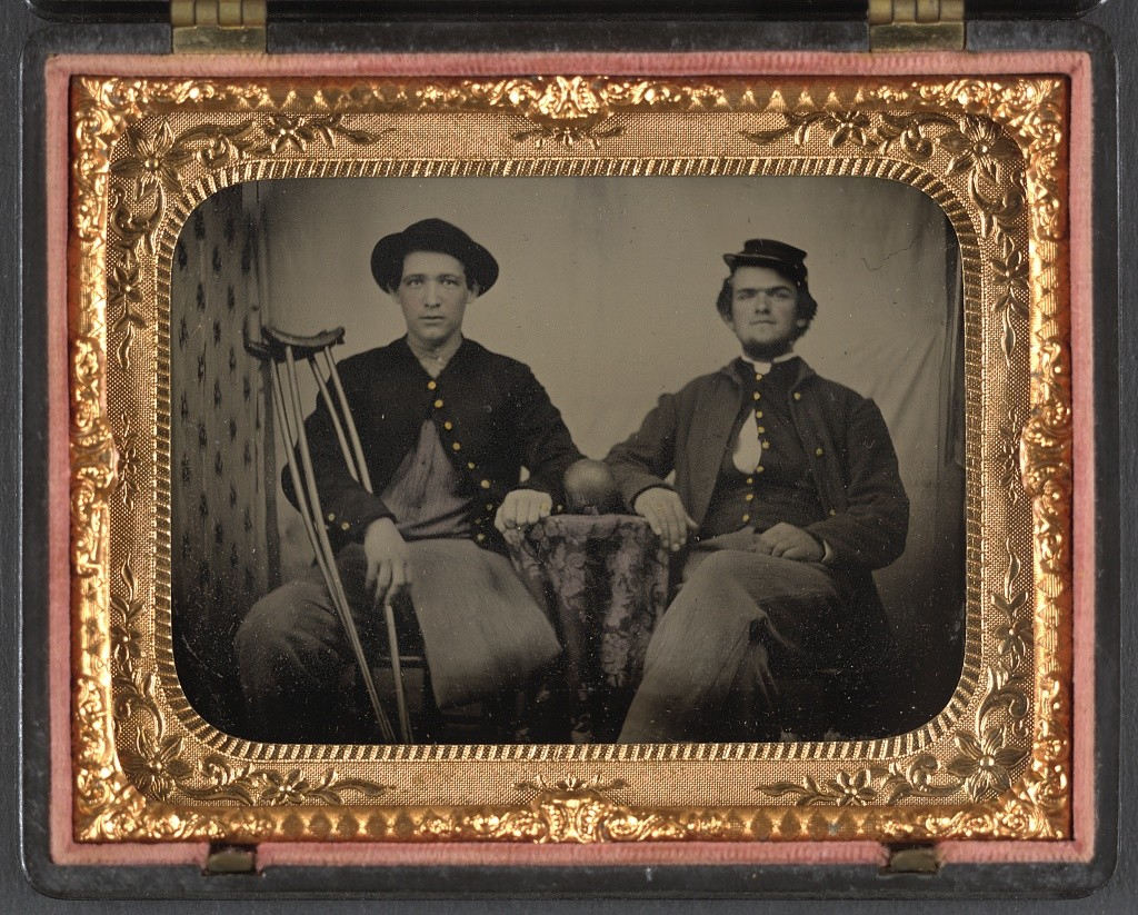 Two unidentified soldiers in Union private's uniforms sitting next to table with cannon ball on top; one soldier has an amputated leg and holds crutches (between 1861 and 1865; LOC: http://www.loc.gov/item/2012648229/)