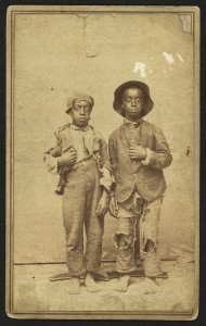 Two African American boys, full-length portrait, facing front] / J. R. Shockley, photographer, West Side of Main St., Hannibal, Mo. (between 1860 and 1865; LOC: http://www.loc.gov/item/2010647915/)