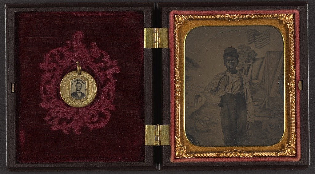 Unidentified African American boy standing in front of painted backdrop showing American flag and tents ; campaign button with portraits of Lincoln on one side and Johnson on the opposite side are attached to inside cover of case (between 1861 and 1865; LOC: http://www.loc.gov/item/2010648377/)