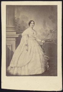 Mrs. Jefferson Davis, full-length studio portrait, standing, facing slightly right with left hand resting on the back of a chair (between 1860 and 1870; LOC: https://www.loc.gov/item/2005677223/)