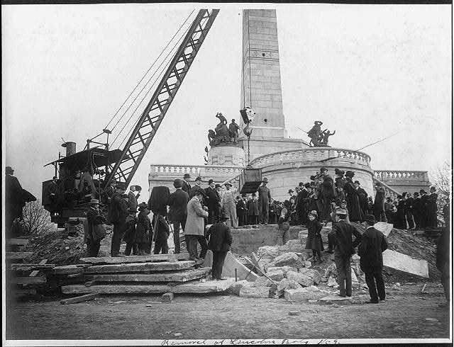 Large crowd watching crane lift box containing Abraham Lincoln's body above grave in front of Lincoln Memorial at Springfield, Ill. (1901; LOC: https://www.loc.gov/item/2005684967/)