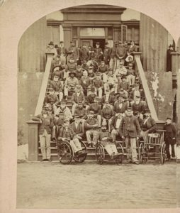 Group of veteran soldiers, National Home for Disabled Volunteer Soldiers, near Fort Monroe, Va., Capt. P.T. Woodfin, Governor (Philadelphia, Pa. : E.H. Hart, Copying, Landscape and Stereoscopic Photographer, 911 Arch Street, [between 1870 and 1880]; LOC: https://www.loc.gov/item/2015649047/)