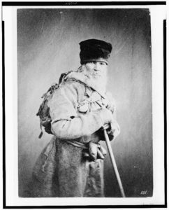 Bearded man, standing, three-quarter length, wearing backpack, with walking stick, Russia (between ca. 1880 and 1924; LOC: https://www.loc.gov/item/93506572/)