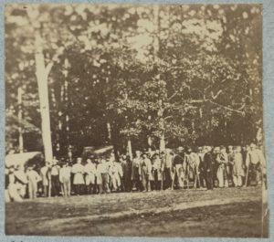 Group of soldiers, some in uniform and some with crutches, pose in front of the woods at the hospital at Camp Letterman in Gettysburg (LOC: https://www.loc.gov/item/2014645949/)